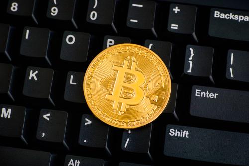 illustration d'une pièce dorée de bitcoin sur un clavier noir